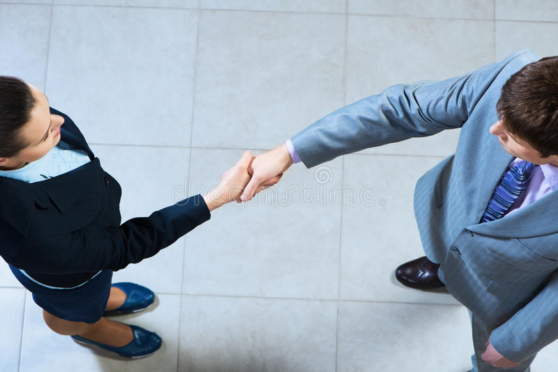 Business woman and businessman shaking hands stock image