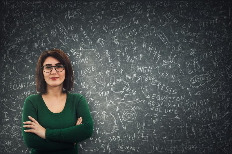 Business woman calculate. Confident businesswoman wearing glasses standing in front of a blackboard solving hard mathematics calculation, economics formula and royalty free stock photography