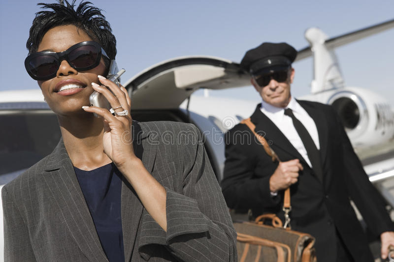 Business Woman On A Call At Airfield. An African American business women communicating on cell phone with driver in the background at airfield royalty free stock images