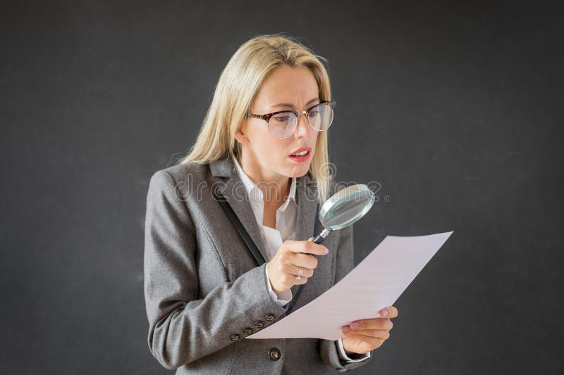 Woman carefully reading business contract with magnifying glass royalty free stock image