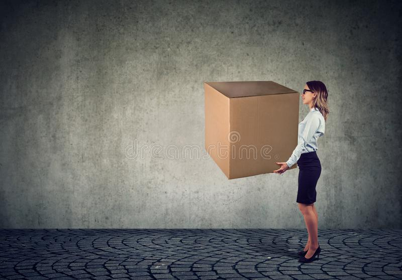 Business woman carrying a huge box royalty free stock images