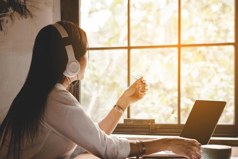 Business woman caucasian working laptop computer and listening music headphone for relax feeling and think about work looking next stock photo
