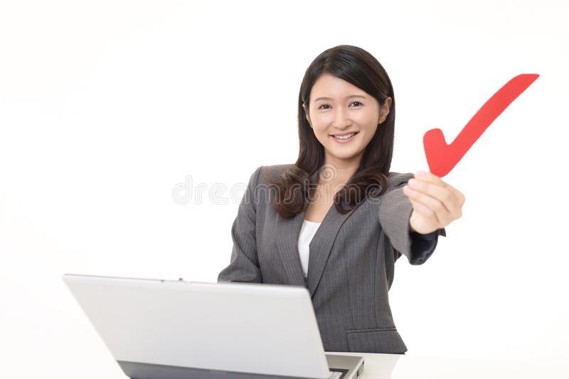 Business woman with a check mark. Business woman working on a laptop stock image