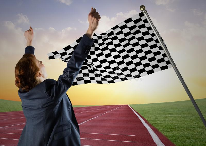 Business woman cheering on track against checkered flag and evening sky stock photo