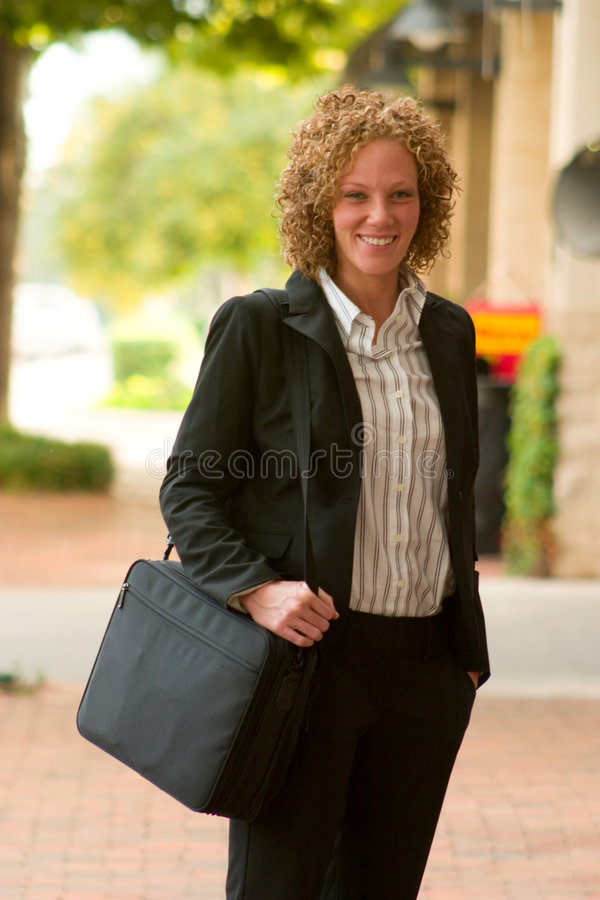 Business Woman In The City 12. Smiling business woman carrying a briefcase strolling down a city sidewalk stock photography