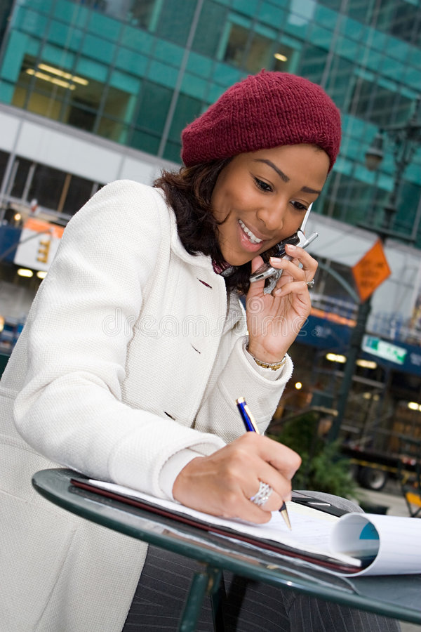 Business Woman In The City. An attractive business woman talking on her cell phone while seated outdoors in the city stock images