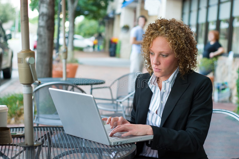 Business Woman In The City 8. Young business woman deep in thought sitting in a chair on a city sidewalk looking at a laptop computer screen royalty free stock photo