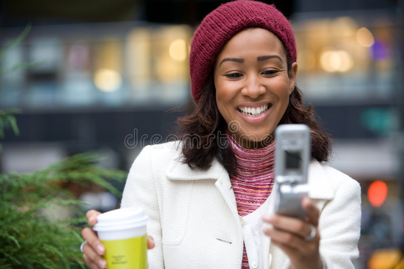 Business Woman In The City. An attractive business woman checking her cell phone in the city. She could be text messaging or even browsing the web via wi-fi or a stock photography