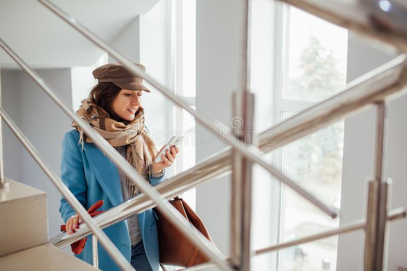 Business woman in coat rises the stairs in the mall. Shopping. Fashion.  stock images