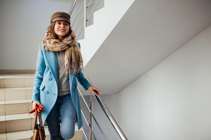Business woman in coat walking down the stairs in the mall. Shopping. Fashion. Business woman in coat rises the stairs in the mall. Shopping. Fashion stock photography
