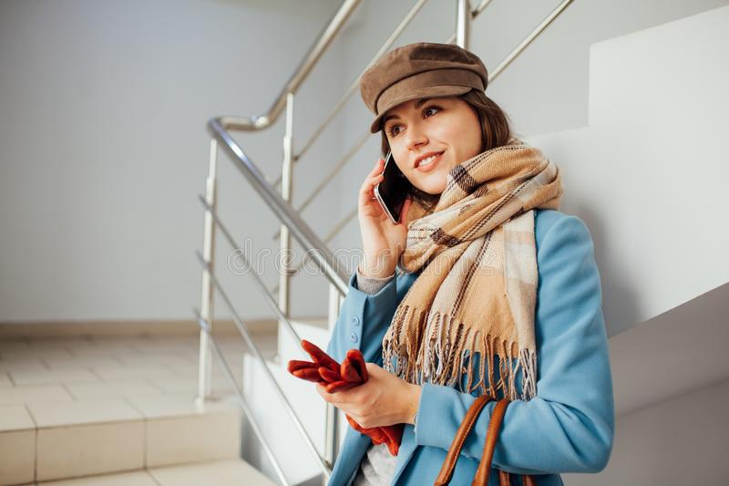 Business woman in coat stands on the stairs in the mall with smartphone. Shopping. Fashion.  royalty free stock photography