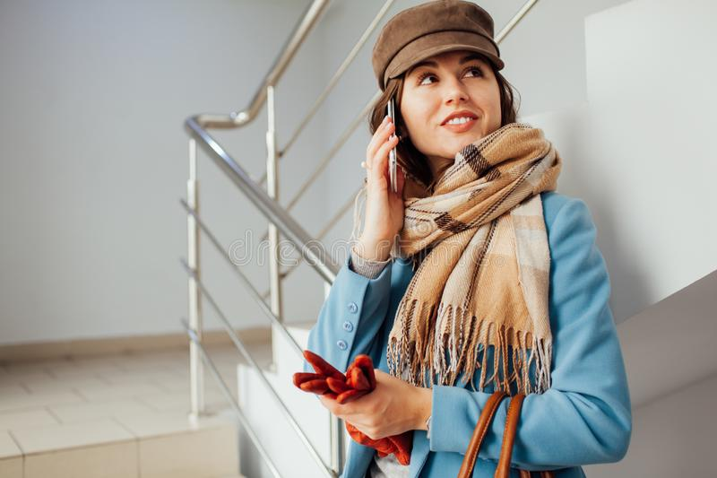 Business woman in coat stands on the stairs in the mall with smartphone. Shopping. Fashion.  royalty free stock photos