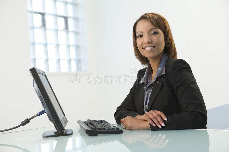 Business Woman with Computer. A business woman sitting at a desk with a computer stock photos