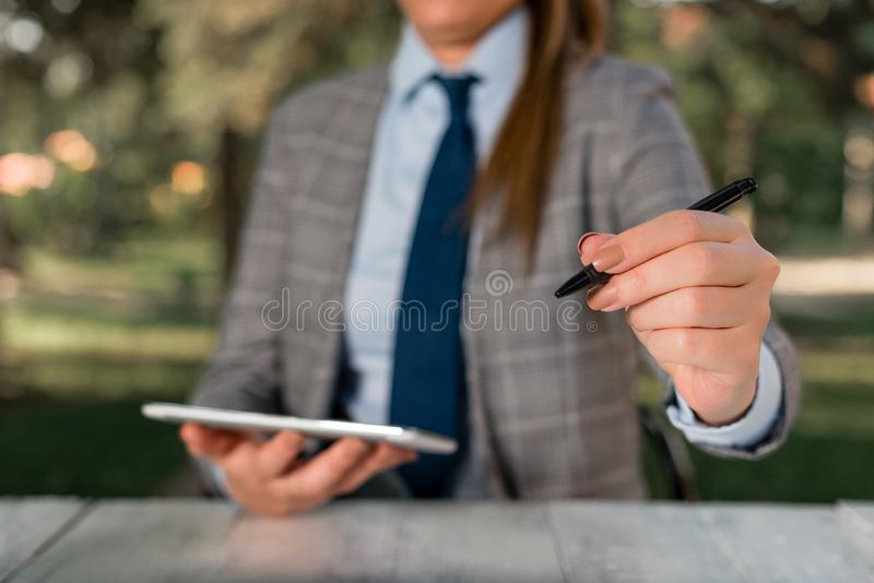 Business woman concept with mobile phone. Business concept with female business person sitting by the table and holding. Business concept with female business royalty free stock images