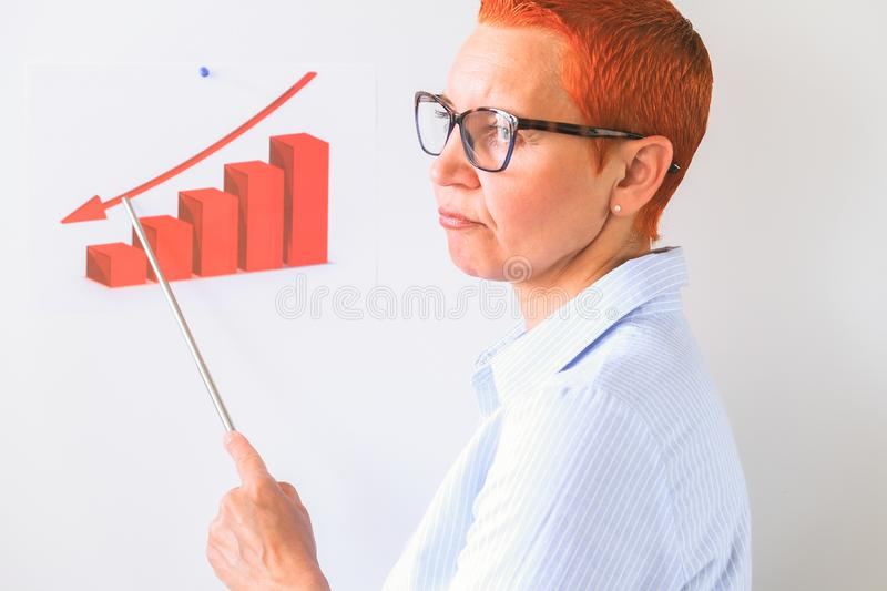 Business woman conducts business training. Business people having on presentation at office. Businessman presenting on the Board stock photo