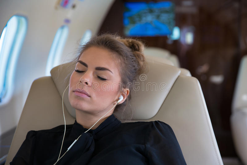 Business woman in a corporate jet relaxing and listening to musi. C with earphones royalty free stock images