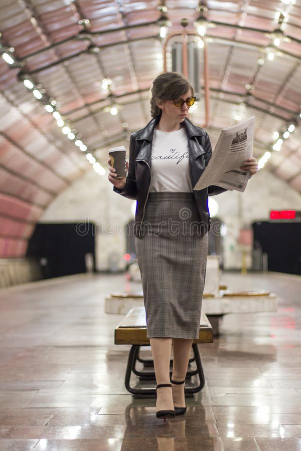 Business woman with a cup of coffee is reading a newspaper. Beautiful girl in a business suit and sunglasses with a cup of coffee stock image