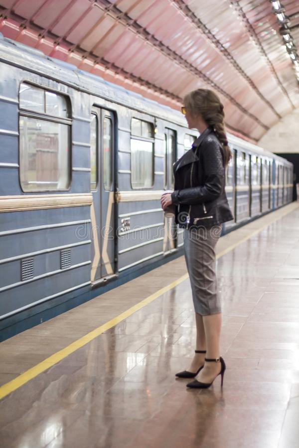 Business woman with a cup of coffee at subway station and train. Beautiful girl in sunglasses and a jacket at the subway station. stock photos