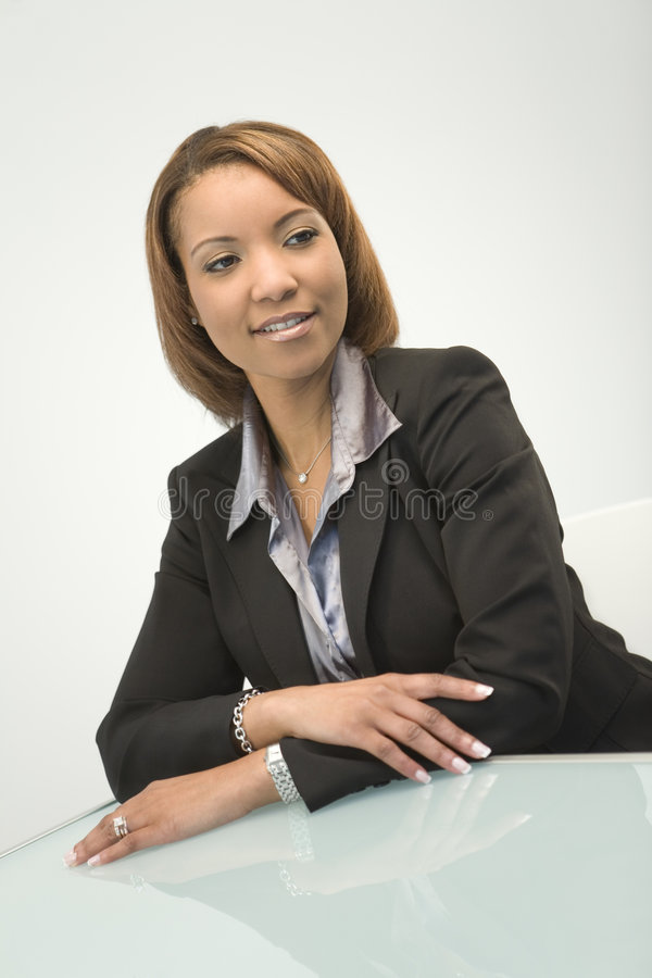 Business Woman at Desk. A business woman sitting at a desk smiling royalty free stock photos