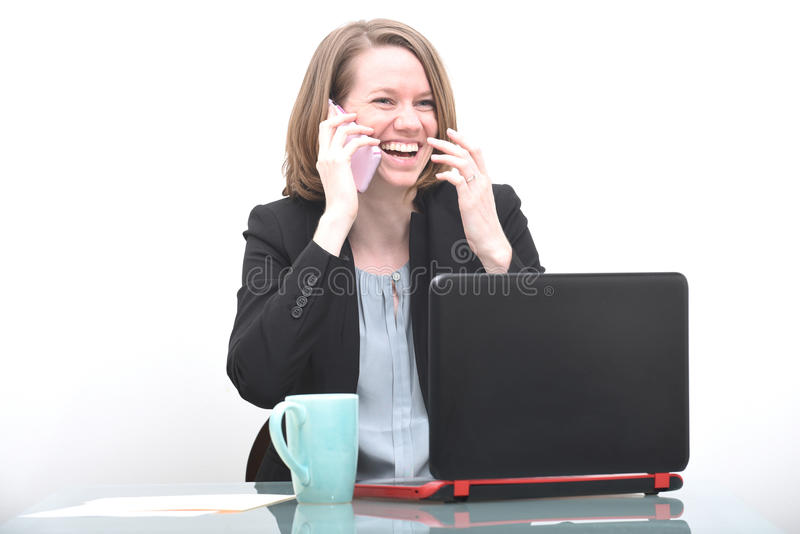 Business woman at desk laughing and talking on phone stock photography