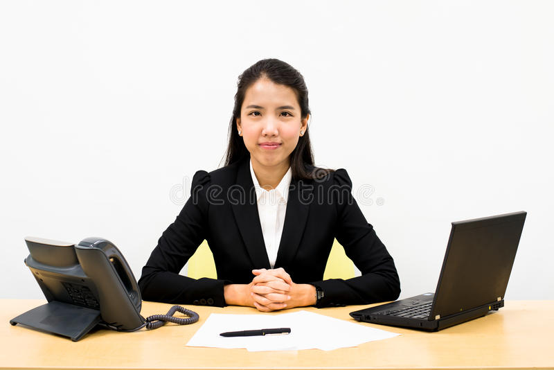 Business woman on a desk. Thai business woman sitting on a desk royalty free stock photography