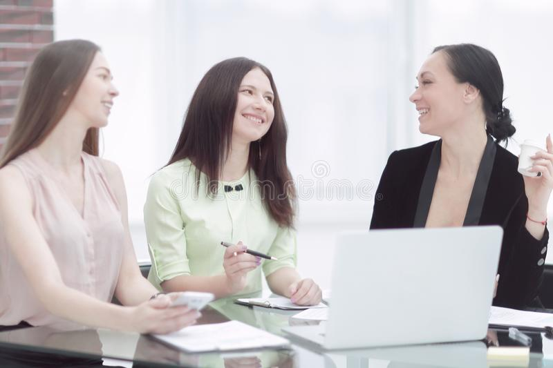 Business woman discussing a document with a female employee when they share a Desk in the office. Business women discussing a document with a female employee stock photo