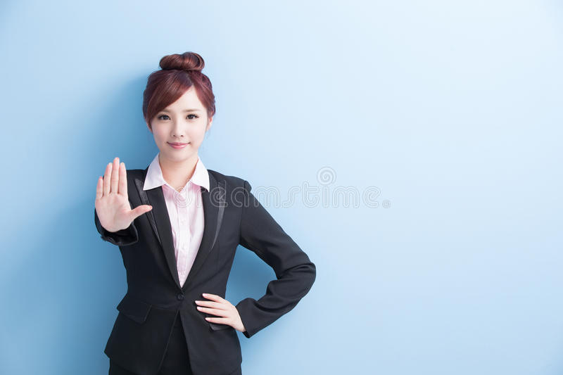 Business woman do stop gesture. Business woman do a stop gesture with on blue background, asian royalty free stock image
