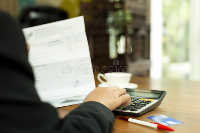 Business woman doing financial calculating bills from credit car stock photography