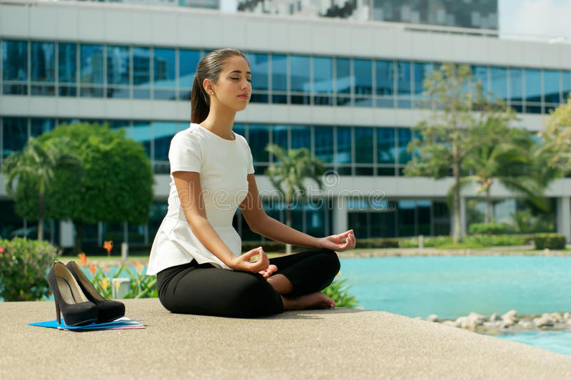 Business Woman Doing Yoga Lotus Position Outside Office Building. Young stressed hispanic business woman doing yoga outside office building, sitting in lotus stock photography