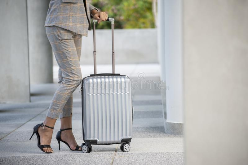 Business woman Dragging suitcase luggage bag,walking to passenger boarding in Airport.Working young woman travel to work.Asian. Tourist female wearing suit pull stock photo