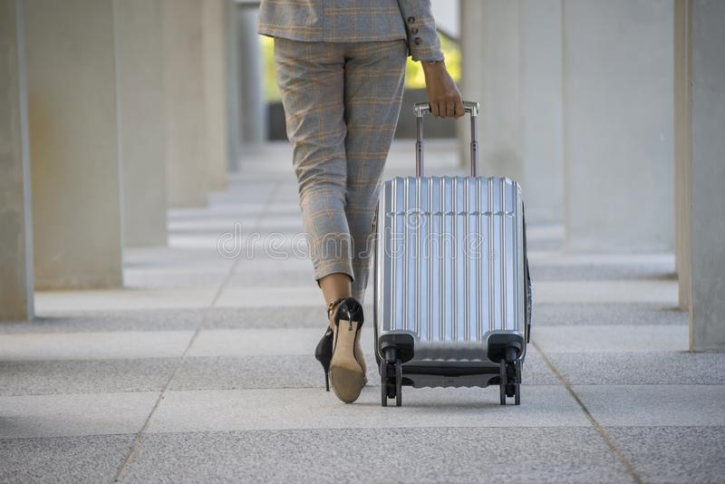 Business woman Dragging suitcase luggage bag,walking to passenger boarding in Airport.Working young woman travel to work.Asian. Tourist female wearing suit pull royalty free stock image