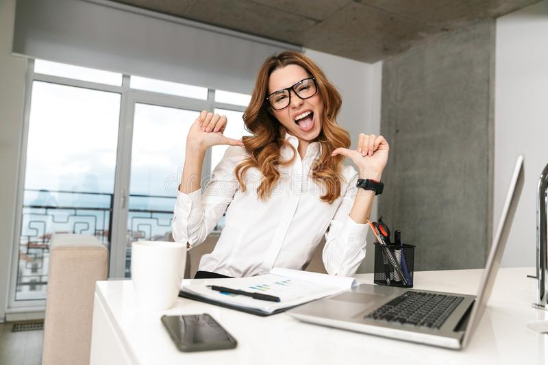 Business woman dressed in formal clothes shirt indoors using laptop computer pointing to herself stock photography