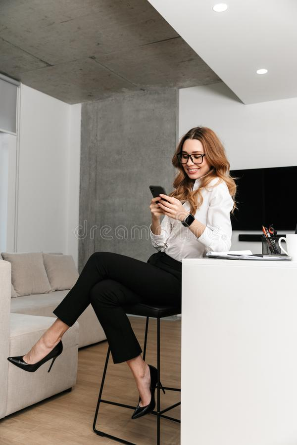 Business woman dressed in formal clothes shirt indoors using mobile phone. Image of young business woman dressed in formal clothes shirt indoors using mobile stock photo
