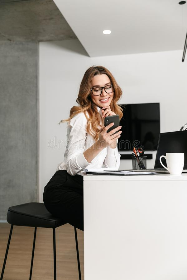 Business woman dressed in formal clothes shirt indoors using mobile phone. Image of young business woman dressed in formal clothes shirt indoors using mobile royalty free stock photos