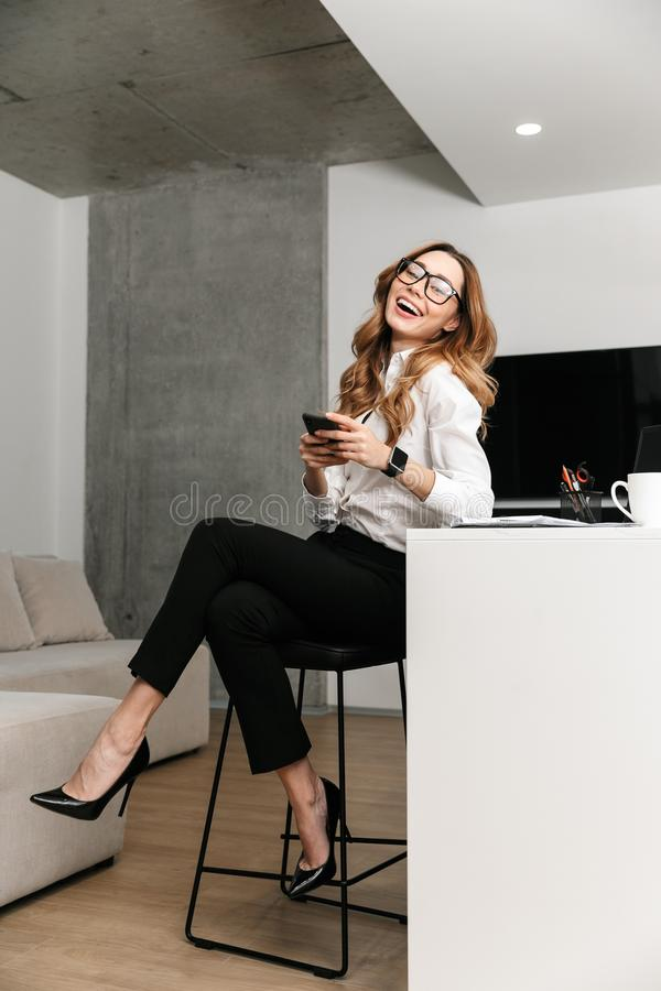 Business woman dressed in formal clothes shirt indoors using mobile phone. Image of young business woman dressed in formal clothes shirt indoors using mobile stock photos