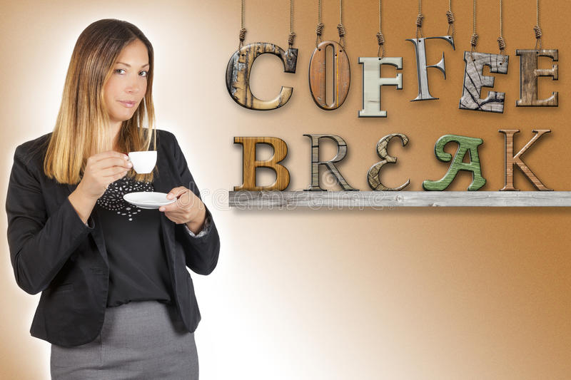 Business woman drinking coffee. Coffee break text word. Work pause. A woman is standing having a coffee during her coffee break. Next to her, on brown gradient royalty free stock images