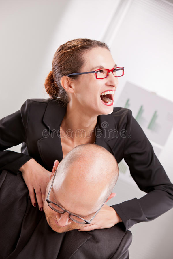 Business woman driven insane hitting a man. Business women driven insane strangling a business man stock images