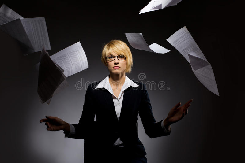Business woman dropping heap of paper. Beautiful young business woman dropping heap of paper royalty free stock photo