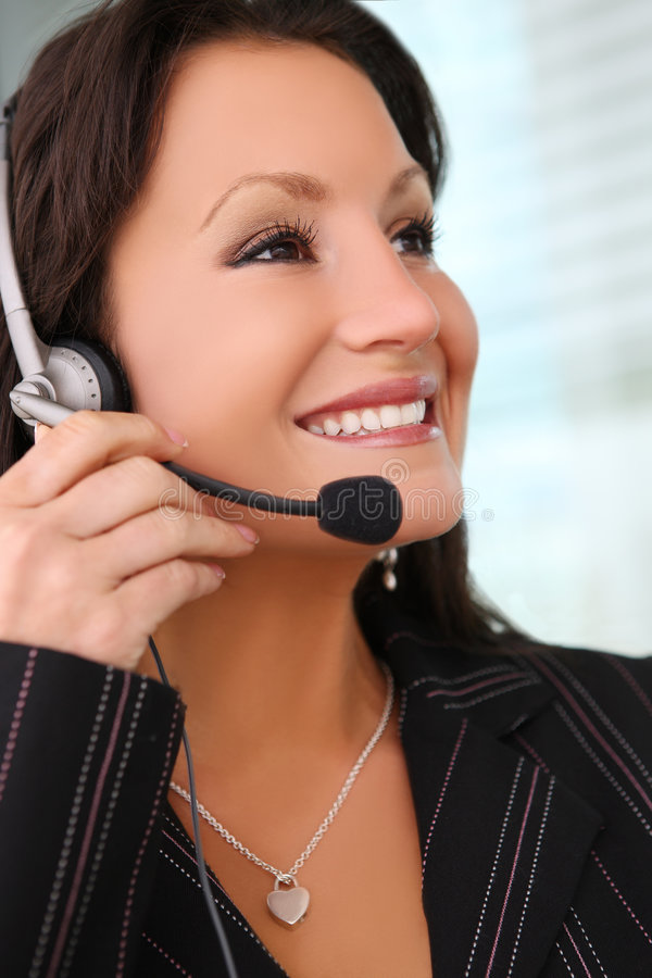 Business Woman With Earphone. A pretty business woman with earphone communicating at office stock image