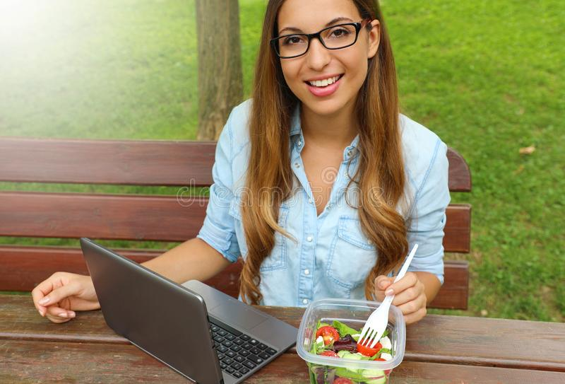 Business woman eating salad on lunch break in city park living healthy lifestyle. Happy smiling young businesswoman take lunch stock photo
