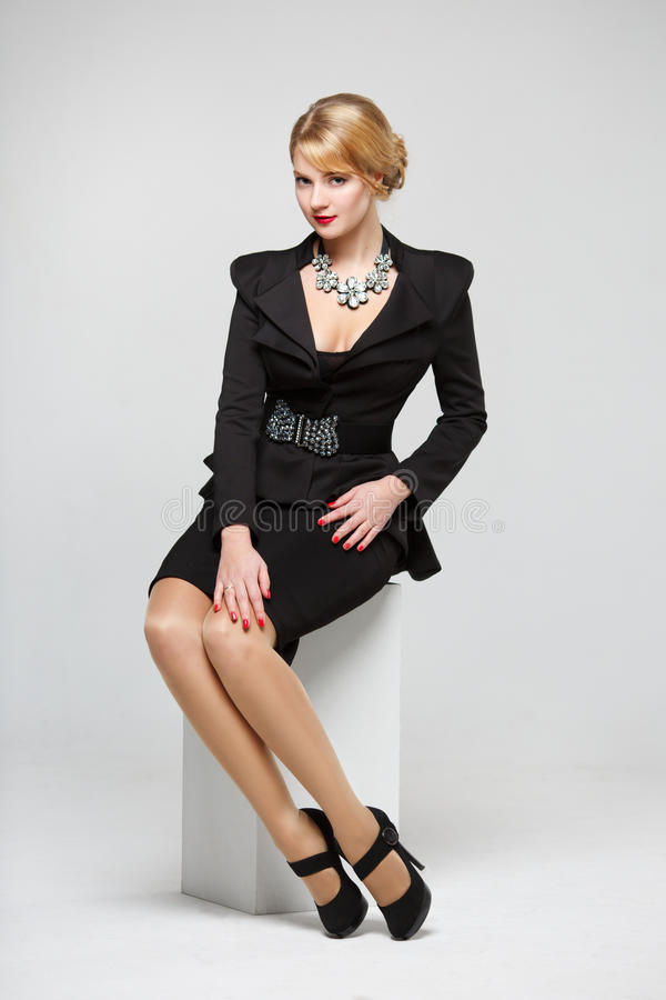 Business woman in an elegant black suit sitting on a white cube royalty free stock photo