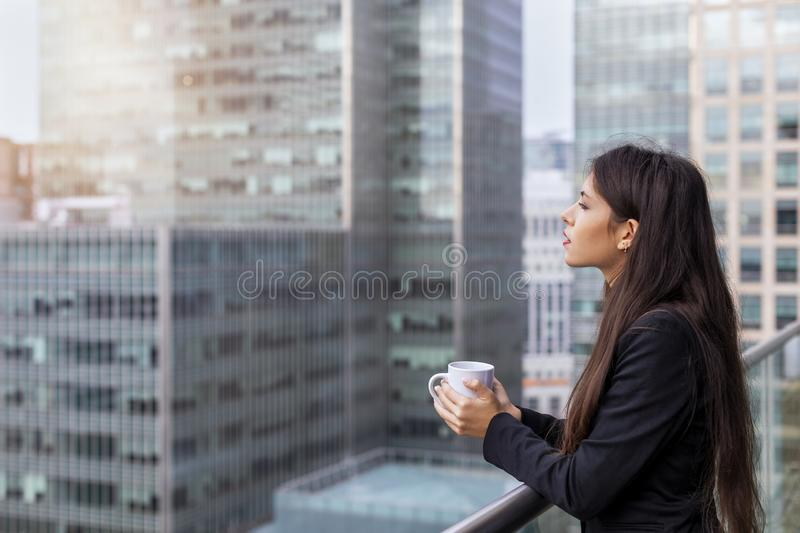 Business woman enjoying her morning break coffee. Outside in front of modern office buildings royalty free stock photo