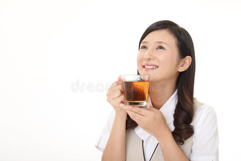 Woman drinking tea. Business woman enjoys cup of tea stock images