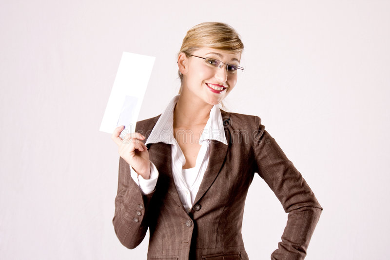 Business woman with an envelope. A young blond business woman with an envelope in her hand royalty free stock photo