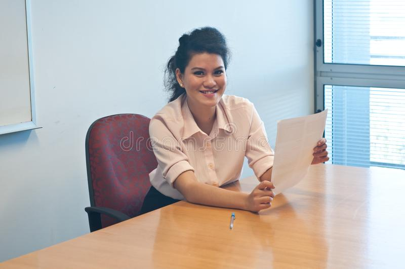 Business woman examining contract agreement in office. And hold it up in hands royalty free stock image