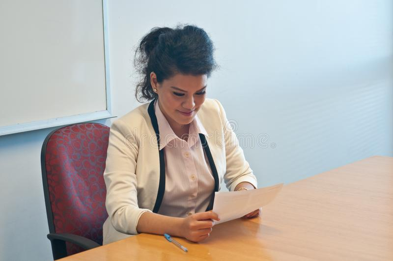 Business woman examining contract agreement in office. Looking at the document and smile royalty free stock photography