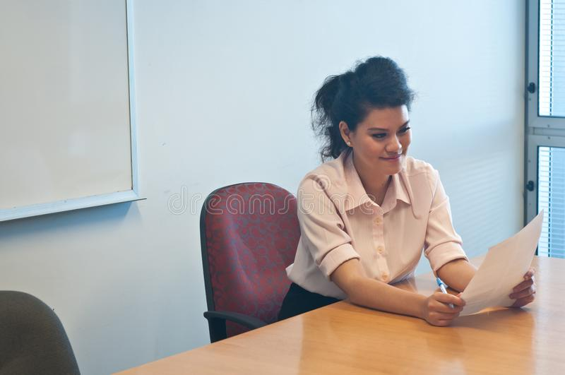 Business woman examining contract agreement in office. And smiling at it stock images