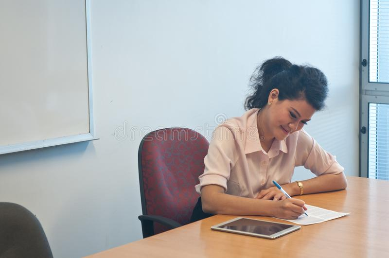 Business woman examining contract agreement in office. Young Asian business woman is examining contract agreement in office royalty free stock image