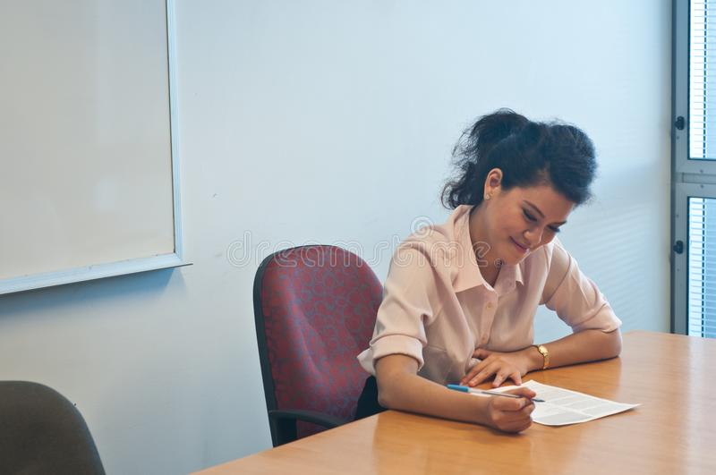 Business woman examining contract agreement in office. Business woman examining before signing a contract agreement in office royalty free stock photography