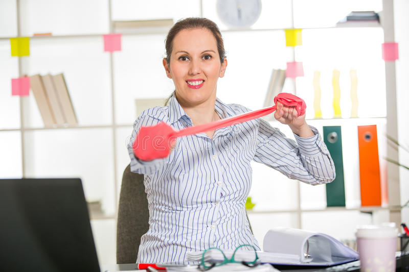Business woman exercise in her office with stripe stretching. Business woman exercise in her office royalty free stock photos